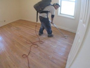 Hardwood Floors Buffing. Vacuum and clean floors before applying the coat.
